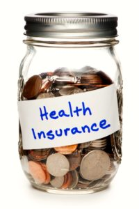 Jar of Coins Labeled Health Insurance on White